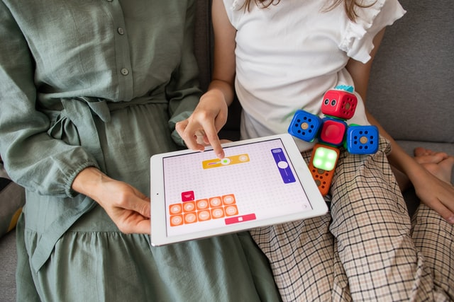 an older person and a child sharing a game on a tablet