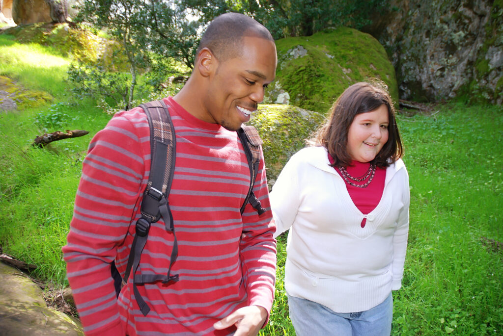 man assisting visually impaired woman on walk