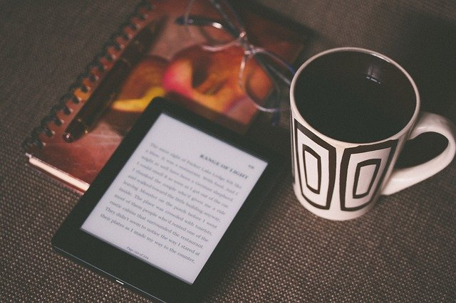 Kindle e-reader, coffee and notepad